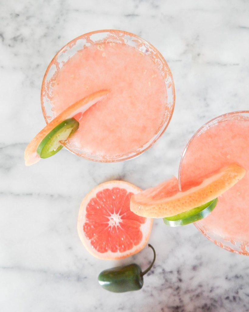 overhead of two pink cocktails with grapefruit and jalapeno wheels