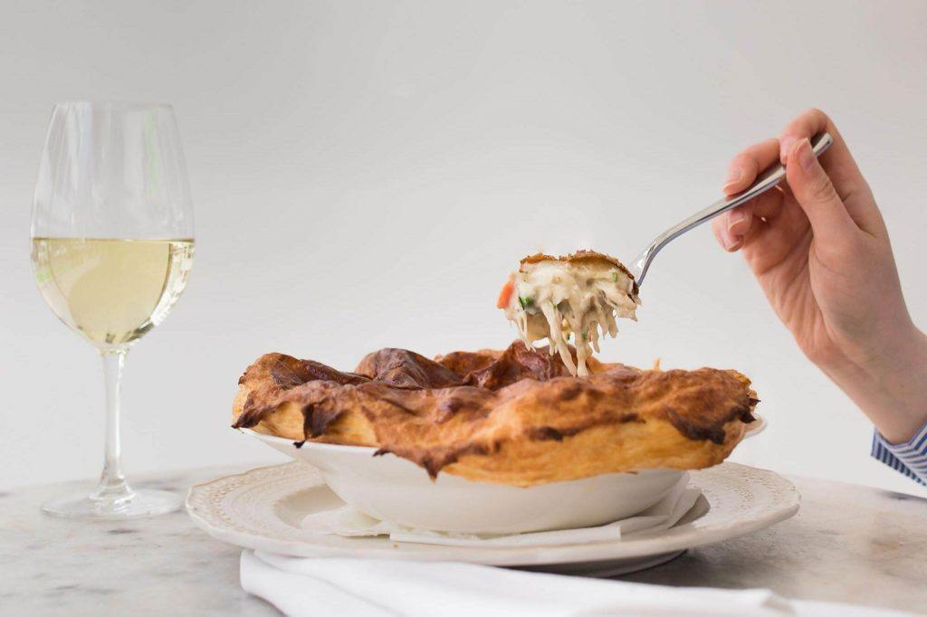 person eating chicken pot pie with a fork with a glass of white wine