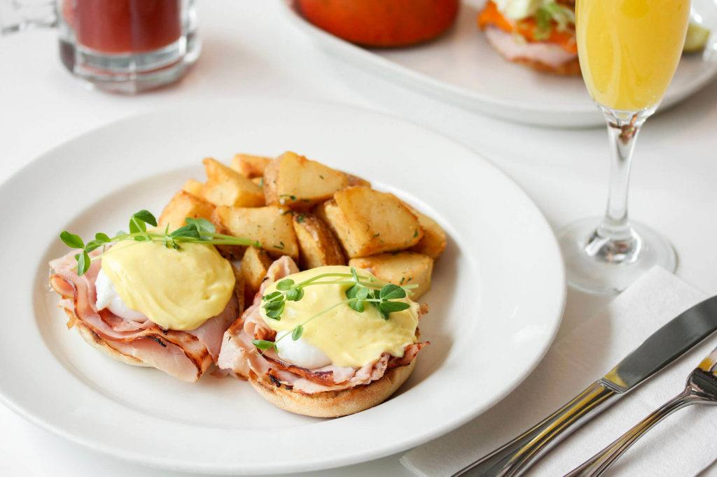 eggs Bnedict with Hollandaise, ham, home fries and a glass of mimosa