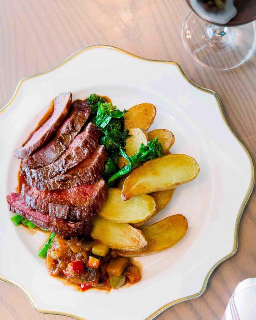 steak frites with broccolini and a glass of red wine