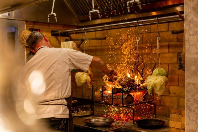 Chef Anthony Walsh cooking in the hearth at Babel