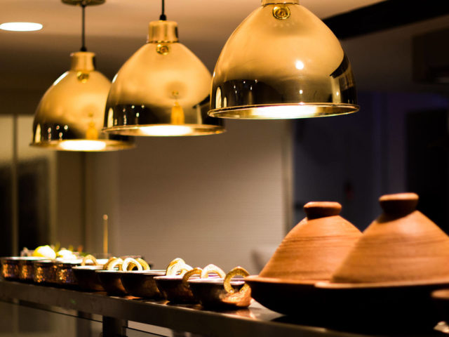 gold lights hanging over copper bowls and tagine cooking vessels