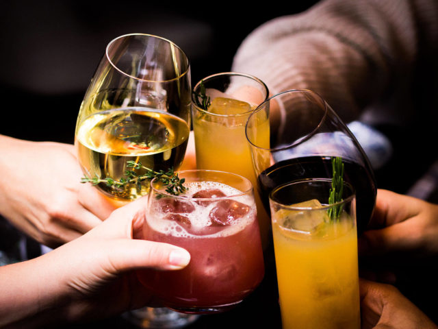 people cheersing mocktails and glasses of wine at Babel