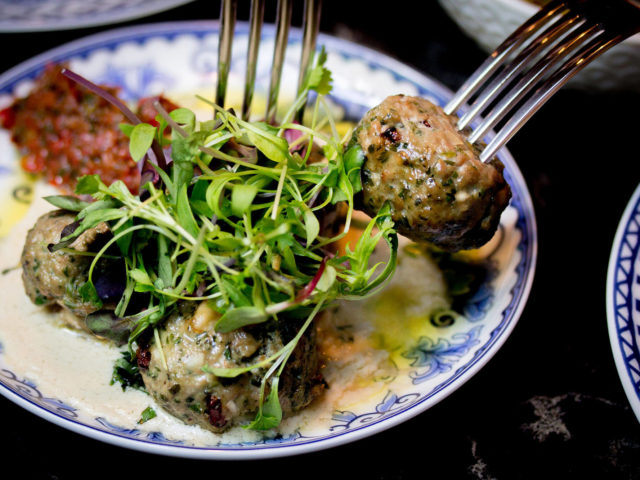 lamb meatballs being picked up on forks in a blue and white bowl