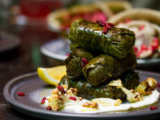 vine leaves garnished with charred cauliflower and pomegranate