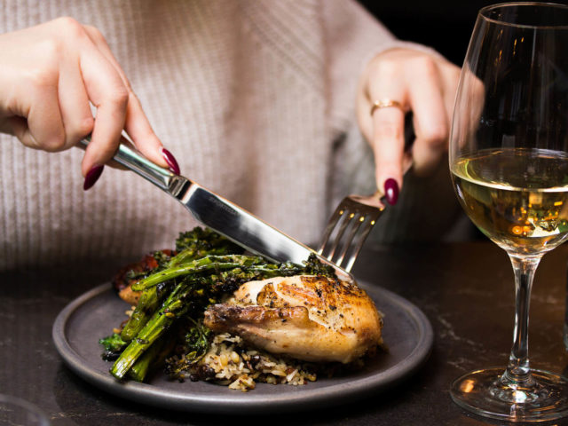guest eating chicken with a glass of white wine