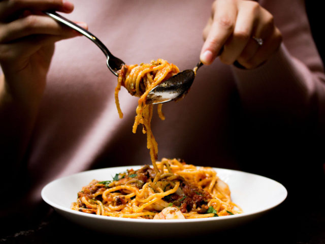 guest twirling spaghetti on a fork and spoon at Babel restaurant