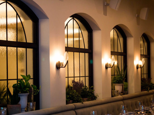 arched windows and wall sconces in the dining room at Babel