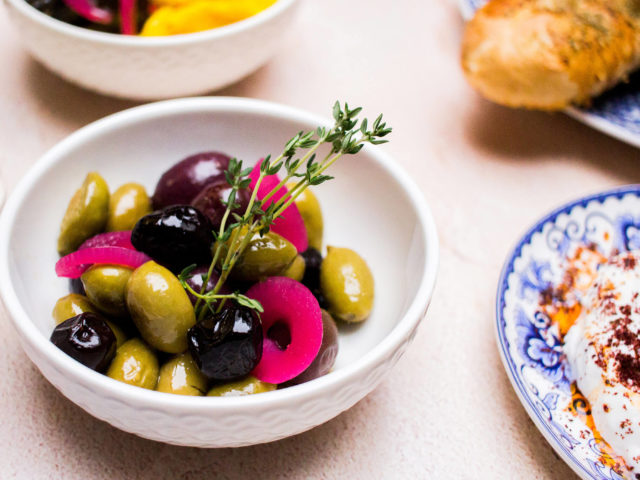 small white bowl of black and green olives, garnished with thyme