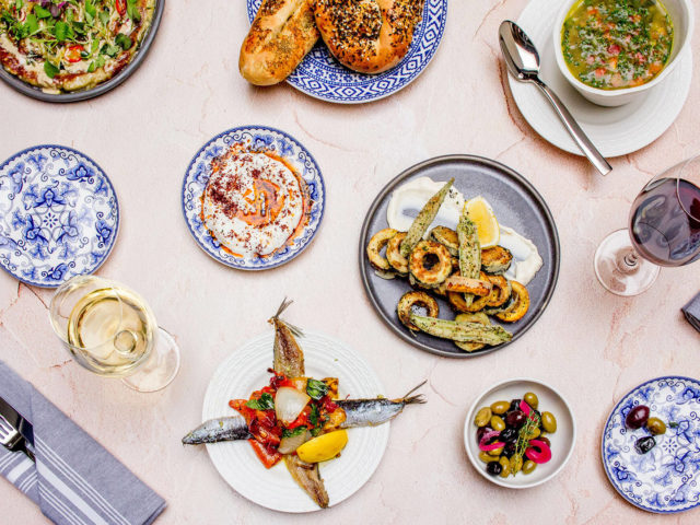 Flatlay of Babel bread, charred eggplant, olives, soup and seafood at Babel restaurant