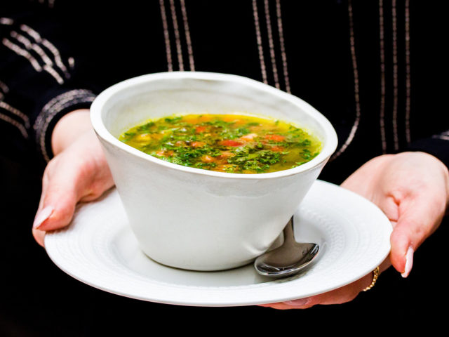 Bowl of mushroom and lentil soup being held by a woman in a black shirt