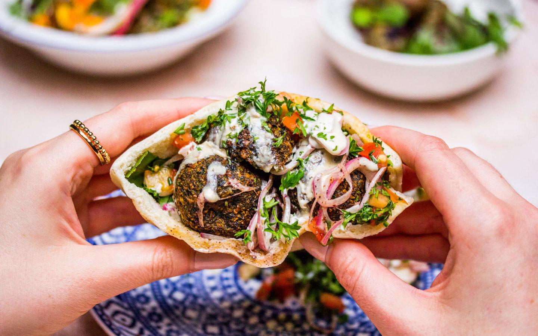 hands holding falafel pita at Babel, a Mediterranean restaurant in Toronto