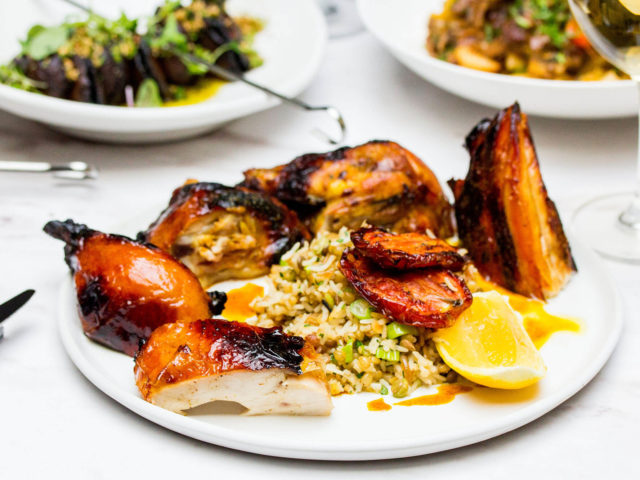 grilled spiced half chicken served with rice, grain and ginger pilaf, on a table with other dinner plates in the background