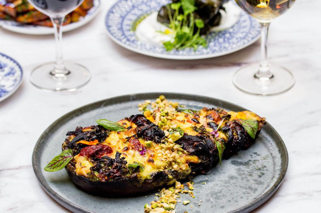 whole stuffed eggplant on a light grey plate