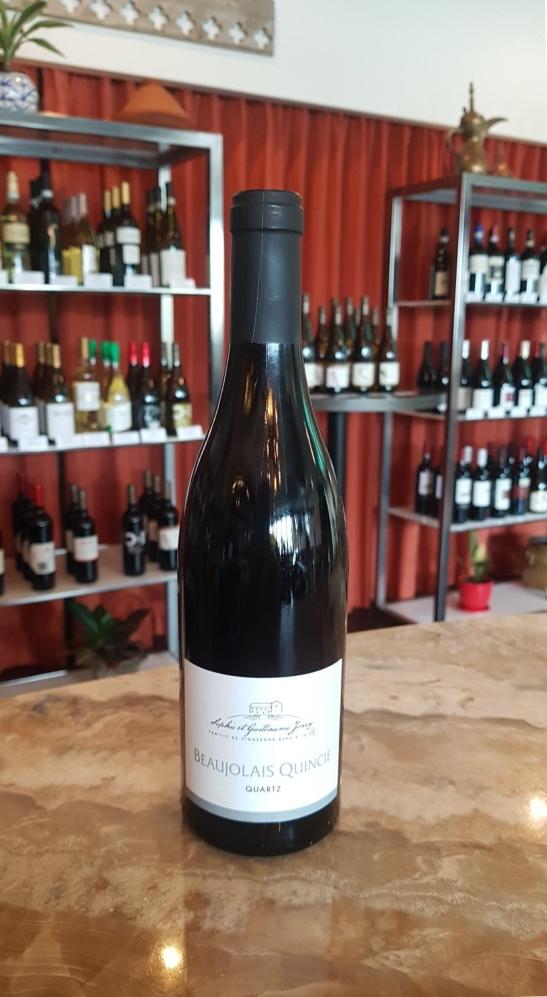 Domaine Joncy Beaujolais Quincié Quartz wine bottle on wood tabletop in front of shelves with wine bottles
