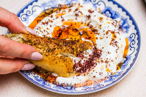 Hand with nail polish dipping bread into a blue and white bowl of labneh