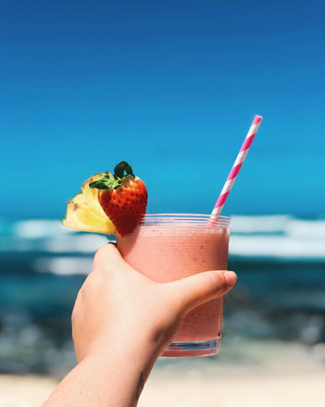 hand holding pink frozen cocktail on beach