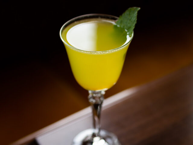 A bright yellow cocktail in a coupe glass sitting on a dark wood table