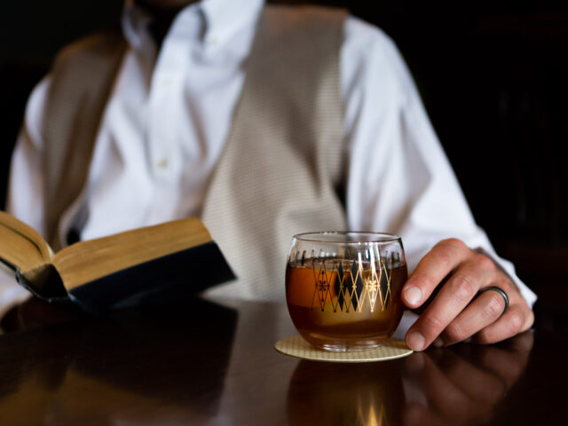 A guest holding an Old Fashioned cocktail while reading a book