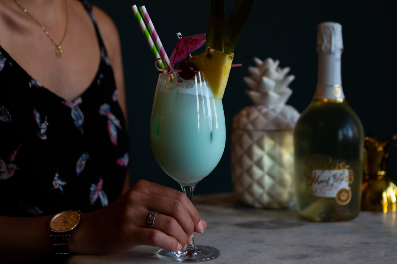 woman holding a blue cocktail with a bottle in the background