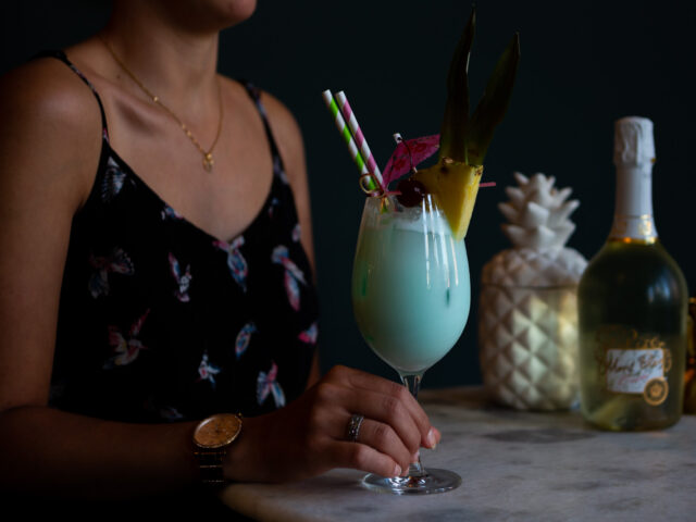 A woman holding a bright blue tropical cocktail garnished with pineapple and a cocktail umbrella