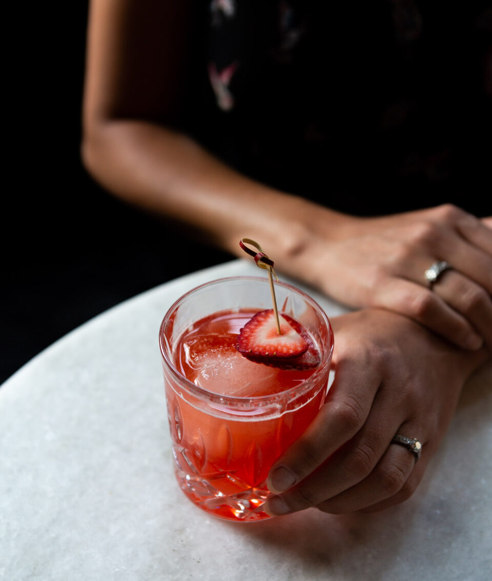 A guest holding a bright red cocktail with a strawberry garnish
