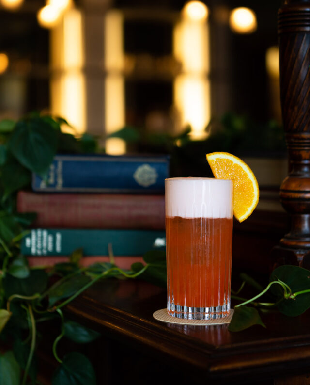 A bright orange cocktail garnished with an orange sitting in front of a stock of books