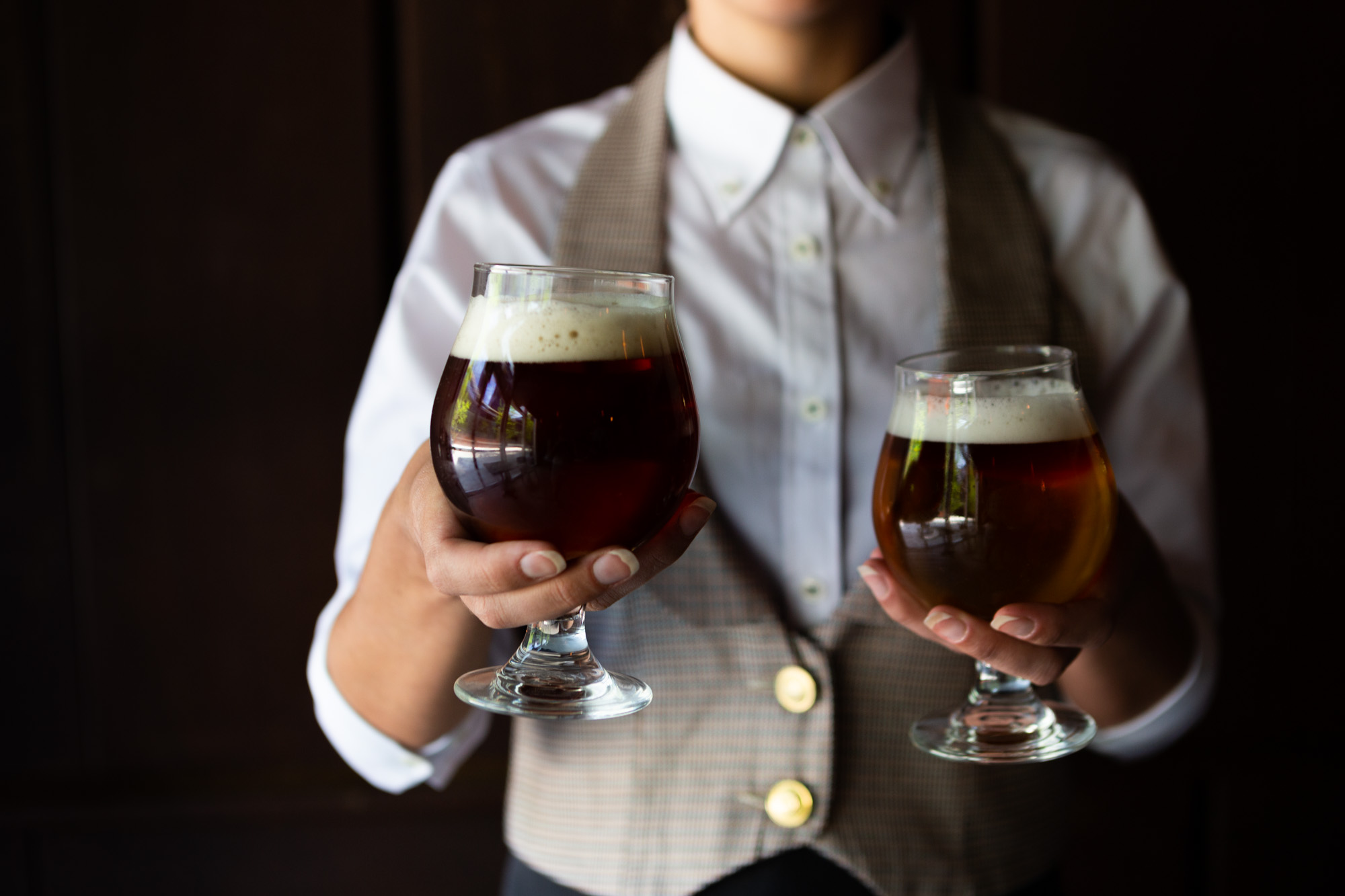 A served hold two craft beers in their hands