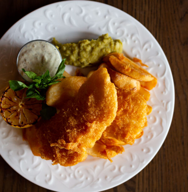 Ale Battered Halibut & Chips on a white plate with a side of tartar sauce, mushy peas and a grilled lemon half