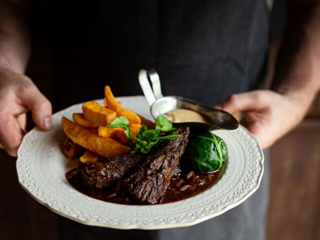 A server holding a plate of Steak & Chips