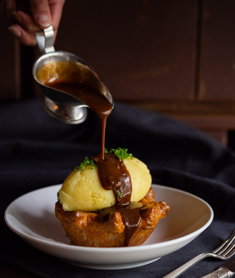 Steak & Mushroom Pie topped with deep gravy & buttermilk mash potato, served in a shallow white bowl