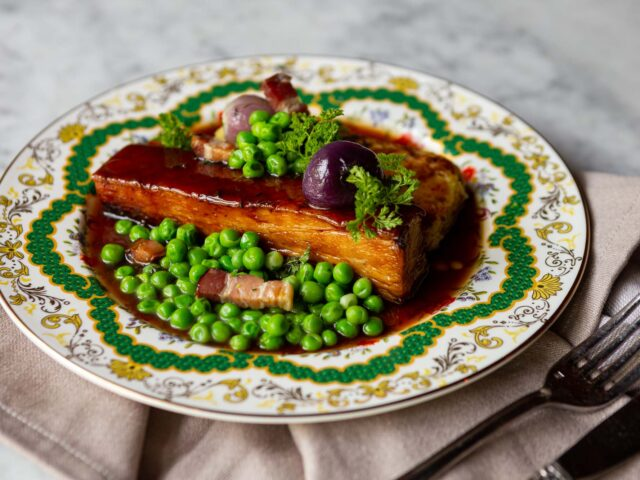 Pork Belly served on a bed of sweet peas, bacon and bubble & squeak croque on a white and green decorative plate