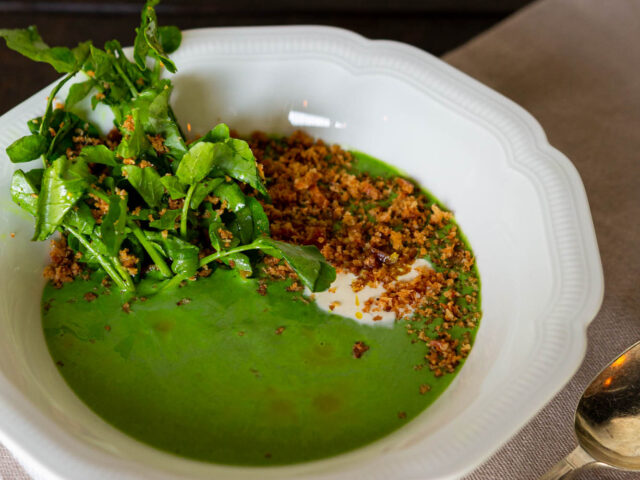 Chilled Watercress Soup in a decorative white bowl topped with bacon crumb, curried oil and crème fraîche
