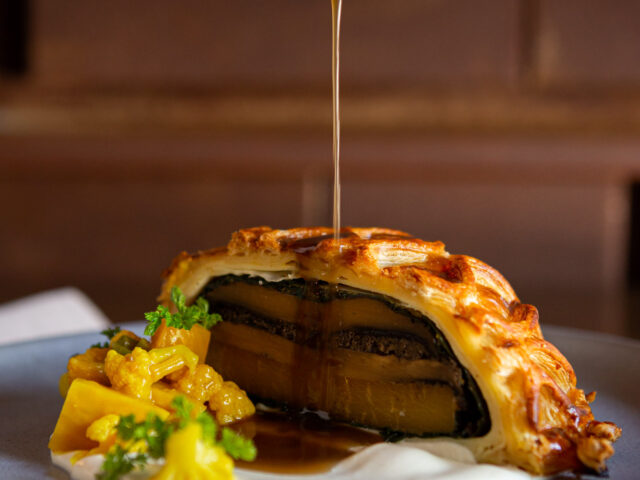 Mushroom Pithivier over cauliflower purée on a dark grey plate with jus being drizzled on top