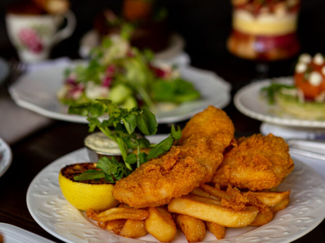 Ale Battered Halibut & Chips on a white plate with a side of tartar sauce and a grilled lemon half
