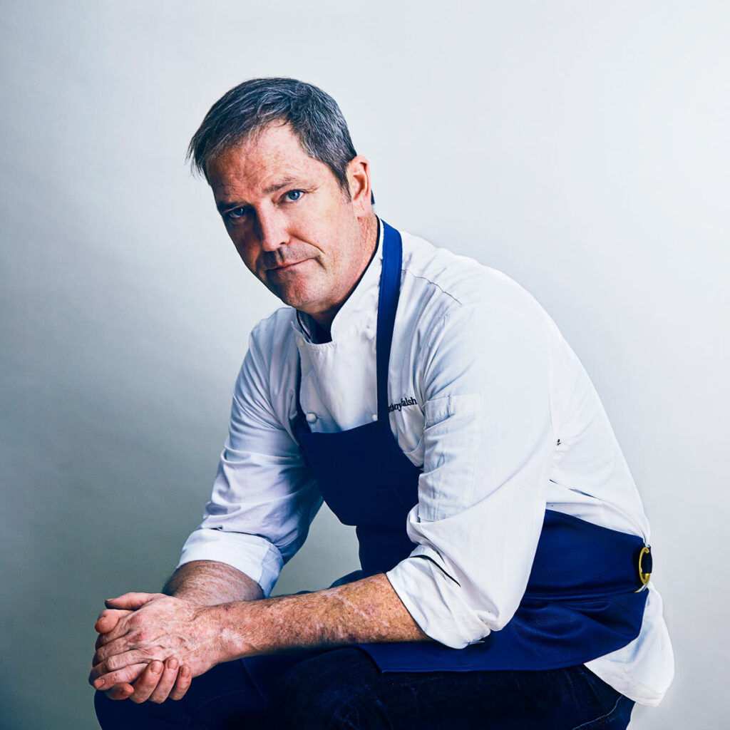 Chef Anthony Walsh in apron and collared shirt sitting on stool