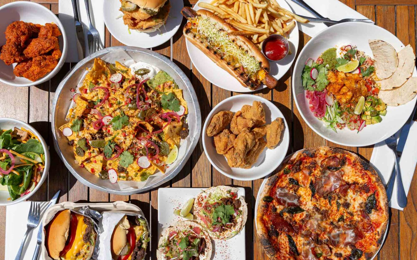 a table filled with various plates of food including nachos, chicken wings, pizza, and hamburgers