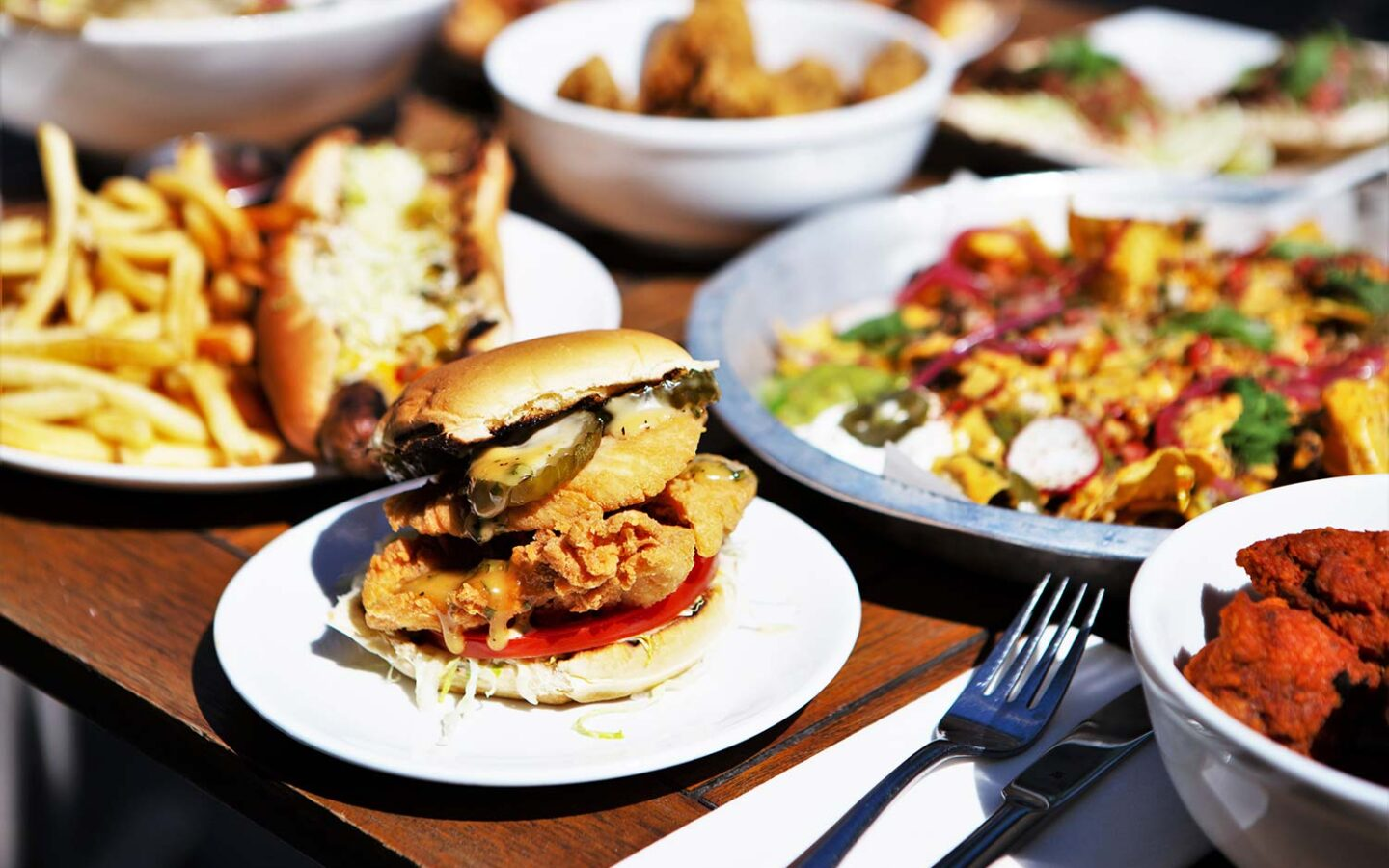 focused shot of crispy fried chicken sandwich on white plate around other meals, from hotdog to nacho platter